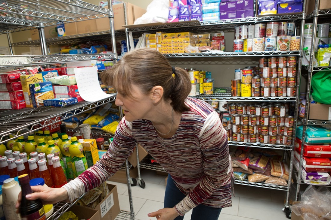 Woman looking through food bank shelves